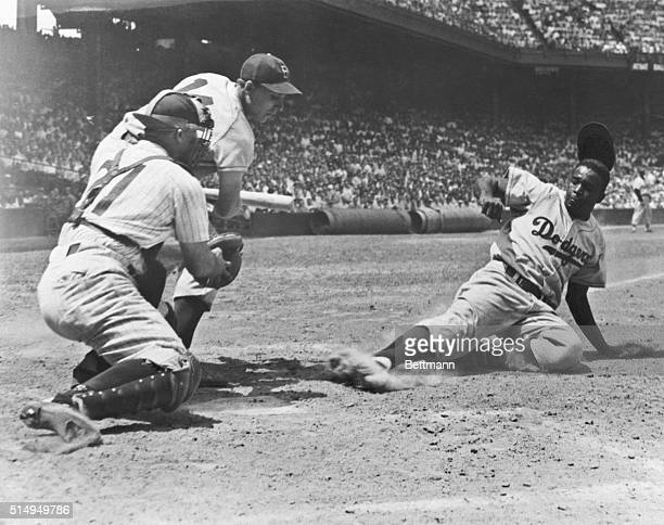 Jackie Robinson of the Brooklyn Dodgers slides home on a steal in the fourth inning of the first game of a double header with the Phillies July 2...