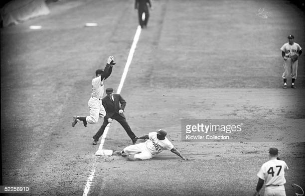 Jackie Robinson of the Brooklyn Dodgers slides into third base ahead of the throw to Gil McDougald of the New York Yankees during a World Series game...