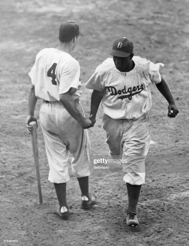 Jackie Robinson of the Dodgers is congratulated here by teammate Pete Reiser as he scored on his homer in the 1st inning of an afternoon game at...
