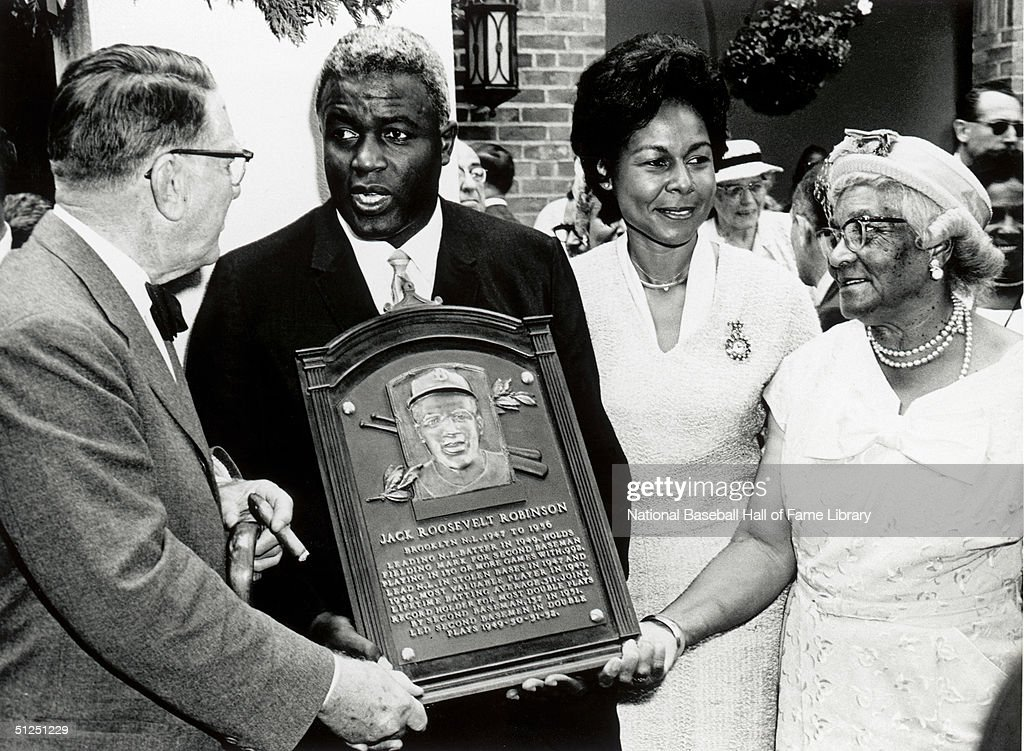 Jackie Robinson poses with his family and the National Baseball Hall of Fame Inductee plaque. Jackie Robinson played for the Brooklyn Dodgers from 1947-1956.