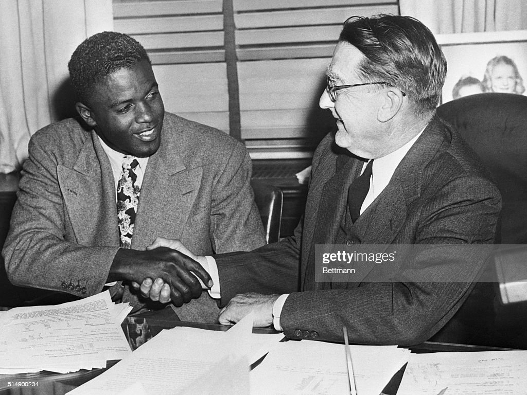 Jackie Robinson shakes Branch Rickey's hand after signing his 1948 contract.