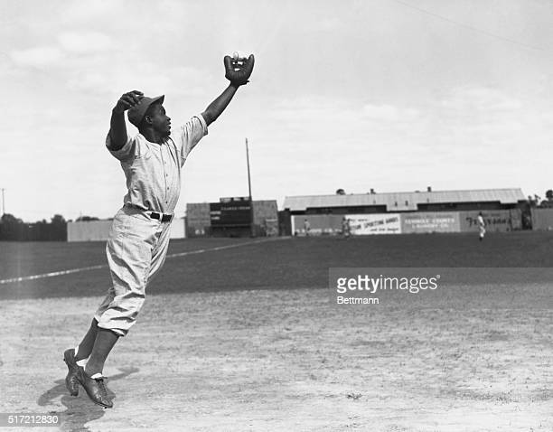 Jackie Robinson stretches for a ball hit through the infield As a member of the Montreal Royals he is the first African American to play in organized...