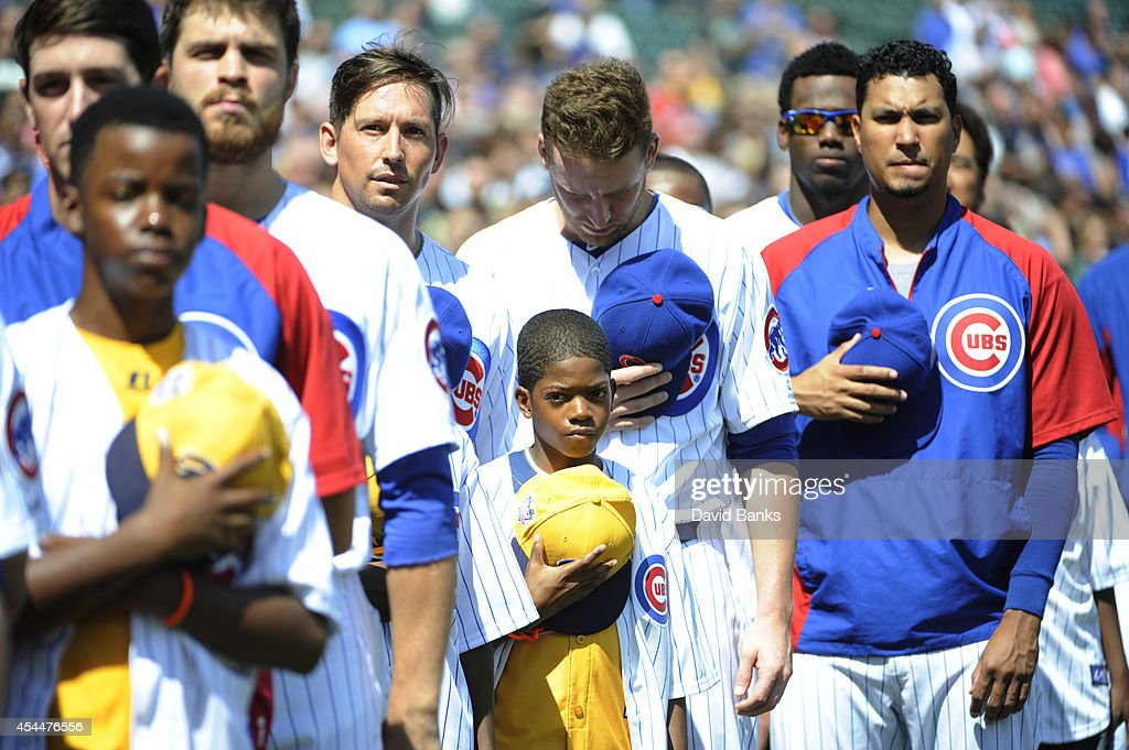 Jackie Robinson West USA Little League Champions from Chicago stand with the Chicago Cubs during the national anthem after being honored before the game against the Milwaukee Brewers on September 1, 2014 at Wrigley Field in Chicago, Illinois.