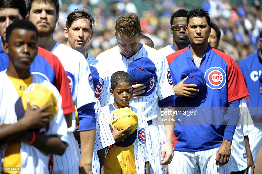 Jackie Robinson West USA Little League Champions from Chicago with the the Chicago Cubs during the national anthem after being honored before the game against the Milwaukee Brewers on September 1, 2014 at Wrigley Field in Chicago, Illinois.