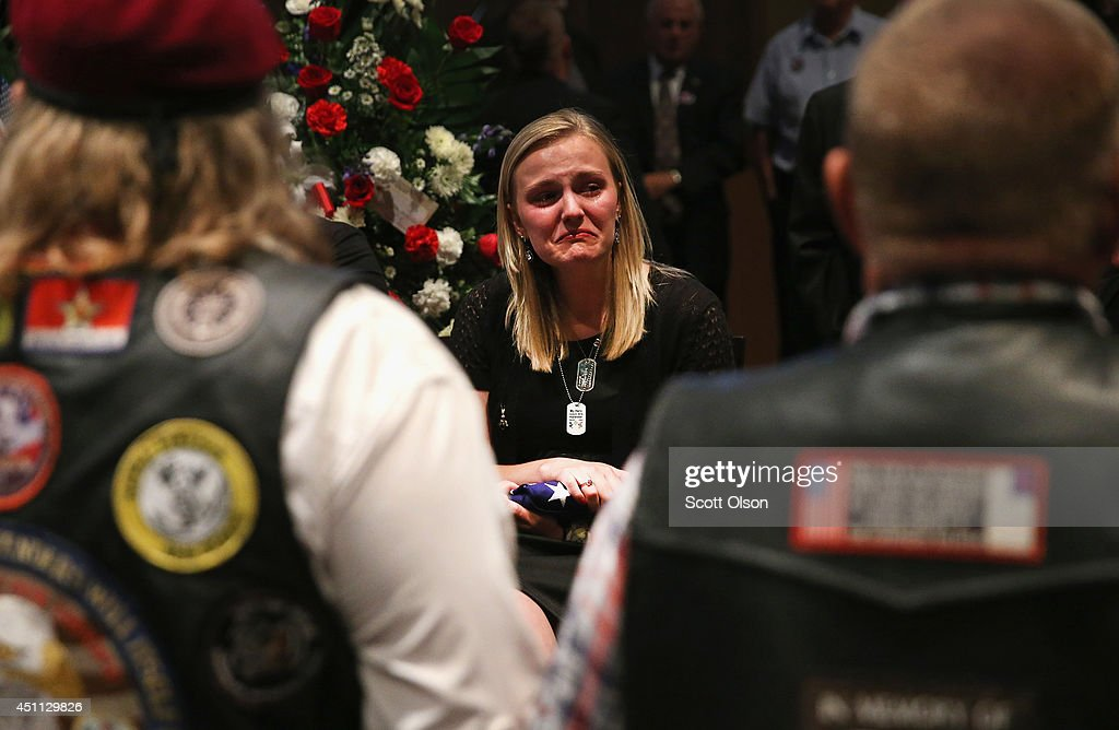 Jackie Rozek fights back tears after she is presented with a flag by members of the Patriot Guard Rider to honor her boyfiriend, U.S. Army Pfc. Aaron Toppen during a visitation at Parkview Christian Church on June 23, 2014 in Mokena, Illinois. Toppen, 19, was killed alongside four other American soldiers and an Afghan soldier in a friendly fire airstrike while they were engaged in a firefight earlier this month in Afghanistan.