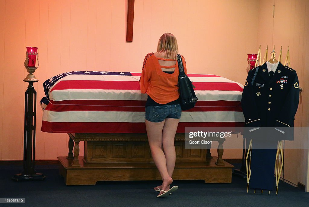 Jackie Rozek spends a quiet moment with the remains of her long-time boyfriend, U.S. Army Pfc. Aaron Toppen in a chapel at Vandenberg Funeral Home on June 22, 2014 in Mokena, Illinois. Toppen, 19, was killed alongside four other American soldiers and an Afghan soldier in a friendly fire airstrike during a firefight earlier this month in Afghanistan. Toppen will be buried on Tuesday in his hometown of Mokena, Illinois.