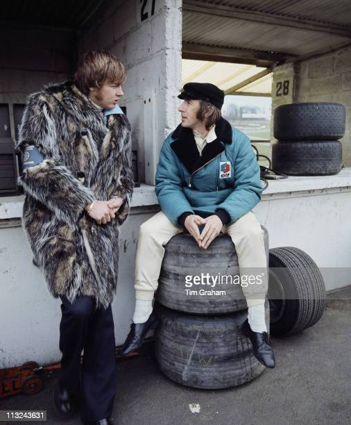 Jackie Stewart driver of the Elf Team TyrrellTyrrell 001 Ford Cosworth DFV 30 V8 sits on a set of tyres talking to Ronnie Peterson dressed in a full...