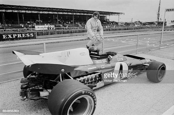 Jackie Stewart of Great Britain driver of the Elf Team Tyrrell Tyrrell 003 Ford Cosworth DFV V8 looks on as Jacky Ickx of Belgium driving the...
