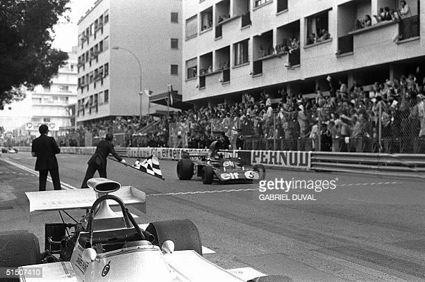 Jackie Stewart triple Formula One champion crosses the finish line 04 June 1973 to win the MonteCarlo Formula One Grand prix At right a Pernod ad
