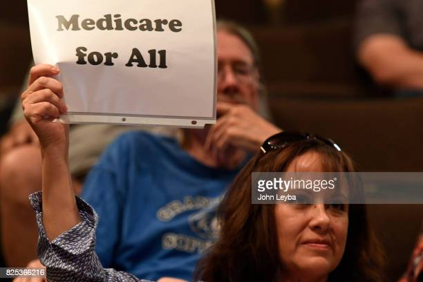 Jackie Wilson of Aurora holds up a sign during US Rep Mike Coffman's town hall at Prairie View High School in on August 1 2017 Henderson