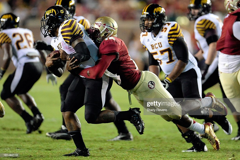 Jackie Wilson #5 of the Bethune-Cookman Wildcats is sacked by Matthew Thomas #12 of the Florida State Seminoles during a game at Doak Campbell Stadium on September 21, 2013 in Tallahassee, Florida.
