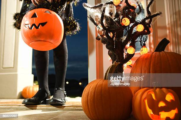 Jack-o-lantern and trick or treater walking through doorway
