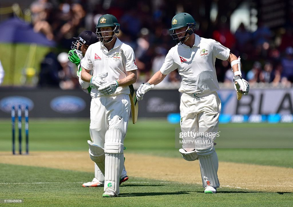 Jackson Bird (R) runs from the field with team mate Adam Voges (L) at the end of the Australian innings during day three of the first cricket Test match between New Zealand and Australia at the Basin Reserve in Wellington on February 14, 2016. / AFP / Marty Melville