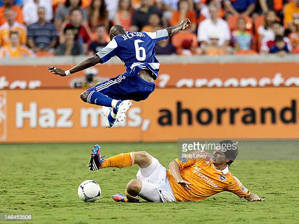 Jackson Goncalves leaps over a sliding Bobby Boswell of the Houston Dynamo in the second half at BBVA Compass Stadium on June 16 2012 in Houston...