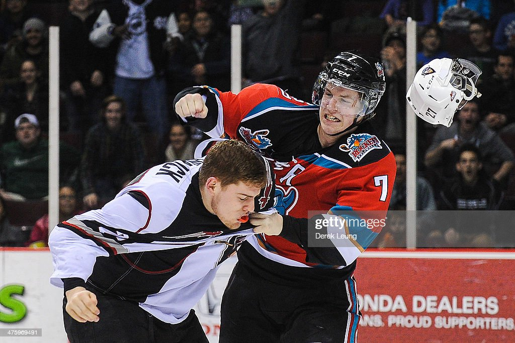 Jackson Houck of the Vancouver Giants loses his helmet after being punched by Damon Severson of the Kelowna Rockets during a WHL game at the Pacific...