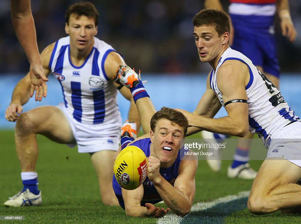 Jackson Macrae of the Bulldogs handballs away from Brent Harvey (L) and Shaun Atley of the Kangaroos during the round 22 AFL match between the North Melbourne Kangaroos and the Western Bulldogs at Etihad Stadium on August 29, 2015 in Melbourne, Australia.