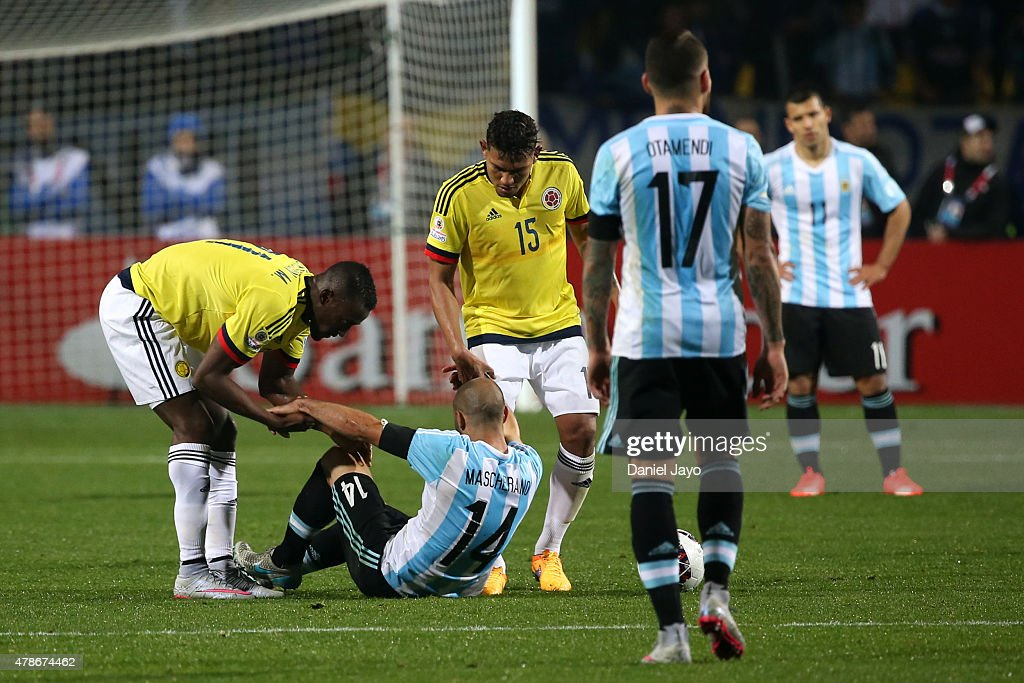 Jackson Martinez (L) and Alexander Mejia of Colombia help to get up Javier Mascherano of Argentina during the 2015 Copa America Chile quarter final match between Argentina and Colombia at Sausalito Stadium on June 26, 2015 in Viña del Mar, Chile.