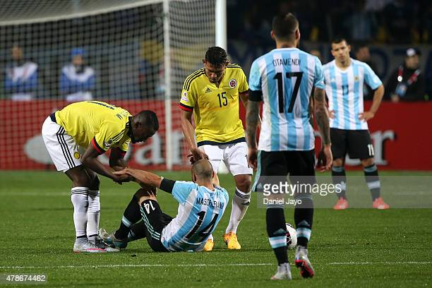 Jackson Martinez and Alexander Mejia of Colombia help to get up Javier Mascherano of Argentina during the 2015 Copa America Chile quarter final match...