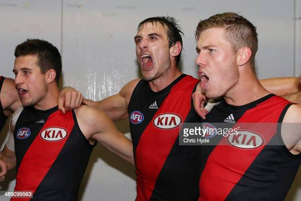 Jackson Merrett Jobe Watson and Jake Melksham sing the team song after winning the round eight AFL match between the Brisbane Lions and the Essendon...