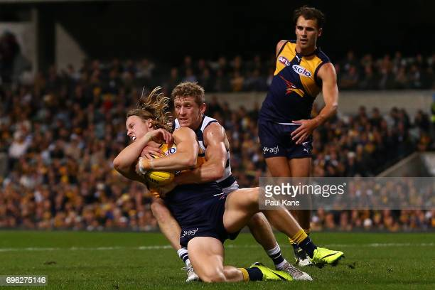 Jackson Nelson of the Eagles gets tackled by Scott Selwood of the Cats during the round 13 AFL match between the West Coast Eagles and the Geelong...