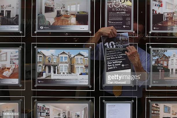 Jacksons Estate Agent employee hangs a promotional sign in their shop front in Dulwich on October 8 2013 in London EnglandThe Government launched...
