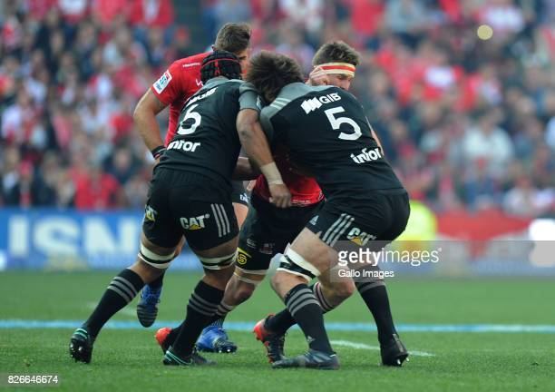 Jaco Kriel of Lions is tackled by Jordan Taufau and Sam Whitelock of Crusaders during the Super Rugby Final match between Emirates Lions and...
