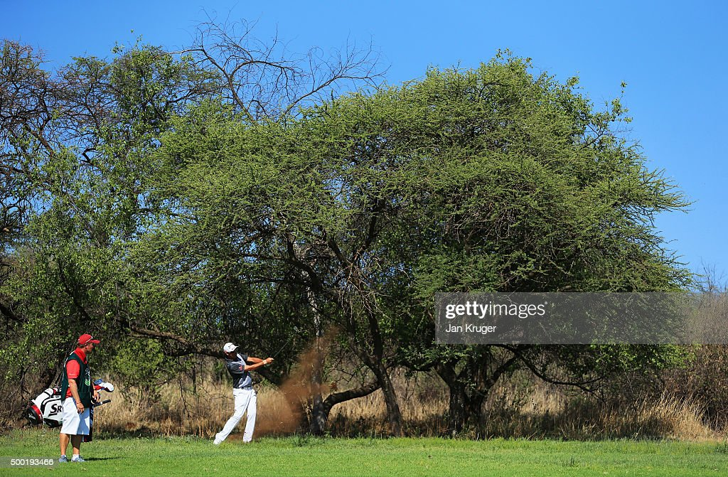 Jaco Van Zyl of South Africa plays out of the rough as caddie John Rawlings looks on during the final round on day four of the Nedbank Golf Challenge...
