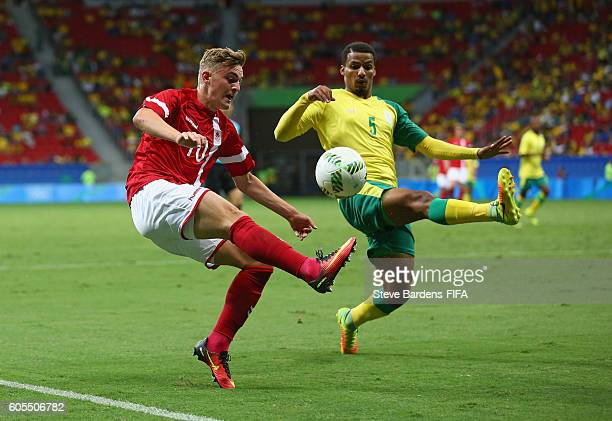 Jacob Bruun Larsen of Denmark chips the ball over Rivaldo Coetzee of South Africa during the Men's First Round Group A match between Denmark and...