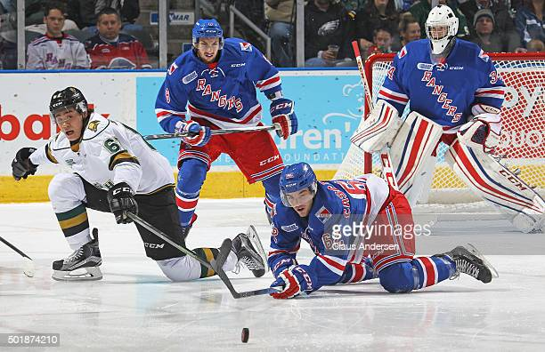 Jacob Cascagnette of the Kitchener Rangers clears a puck away from Kole Sherwood of the London Knights during an OHL game at Budweiser Gardens on...