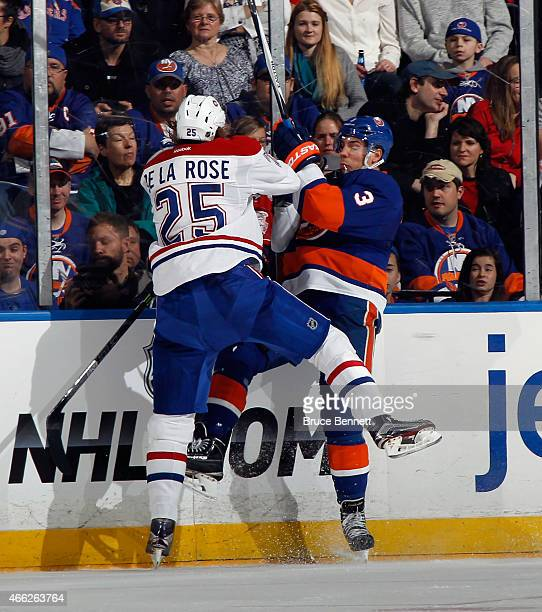 Jacob De La Rose of the Montreal Canadiens hits Travis Hamonic of the New York Islanders into the boards during the first period at the Nassau...
