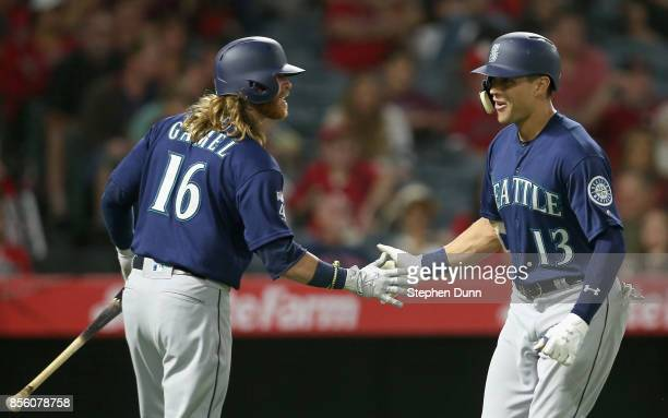 Jacob Hannemann of the Seattle Mariners is greeted by on deck batter Ben Gamel as he returns to the dugout after hitting a solo home run in the fifth...