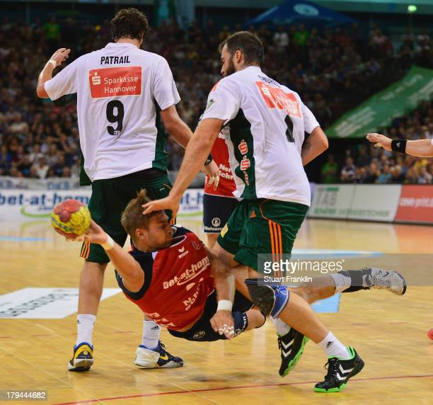 Jacob Heinl of Flensburg challenges for the ball with Mait Patrail and Torge Johannsen of hannover during the DKB Bundesliga handball match between...