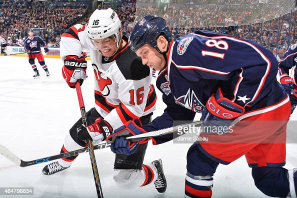 Jacob Josefson of the New Jersey Devils and David Clarkson of the Columbus Blue Jackets battle for a loose puck during the second period on February...