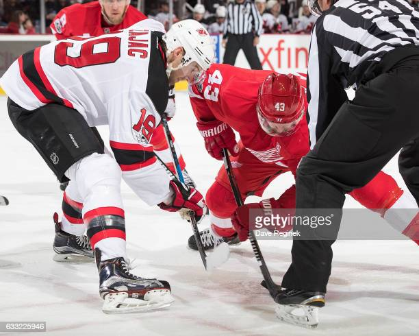 Jacob Josefson of the New Jersey Devils faces off against Darren Helm of the Detroit Red Wings during an NHL game at Joe Louis Arena on January 31...