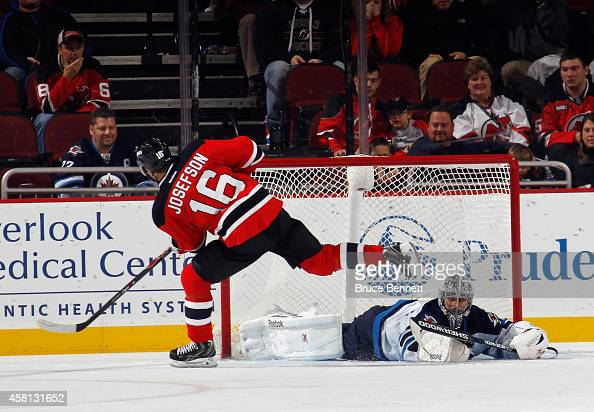 Jacob Josefson of the New Jersey Devils scores the game winning goal during the shootout against Ondrej Pavelec of the Winnipeg Jets at the...