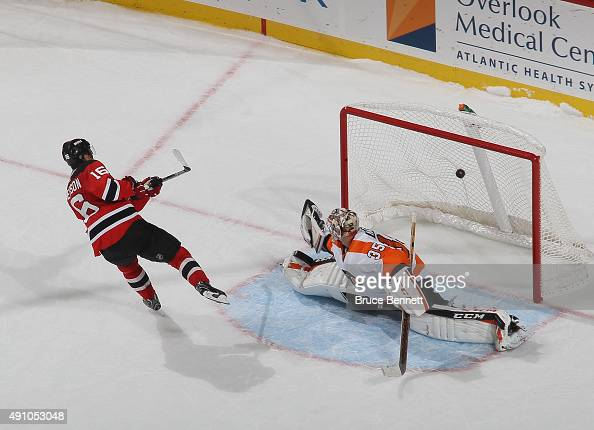 Jacob Josefson of the New Jersey Devils scores the shootout winner over Steve Mason of the Philadelphia Flyers at the Prudential Center on October 2...