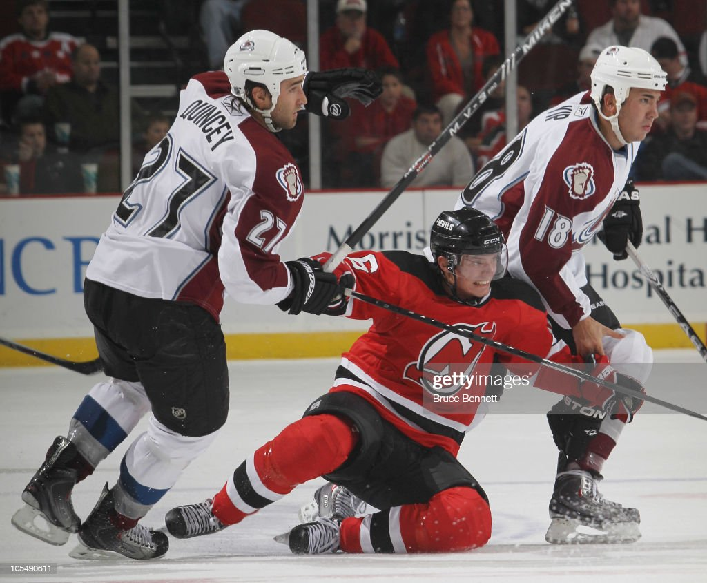 Jacob Josefson of the New Jersey Devils skates in his first NHL game and is sandwiched by Kyle Quincey and Brandon Yip of the Colorado Avalanche at...