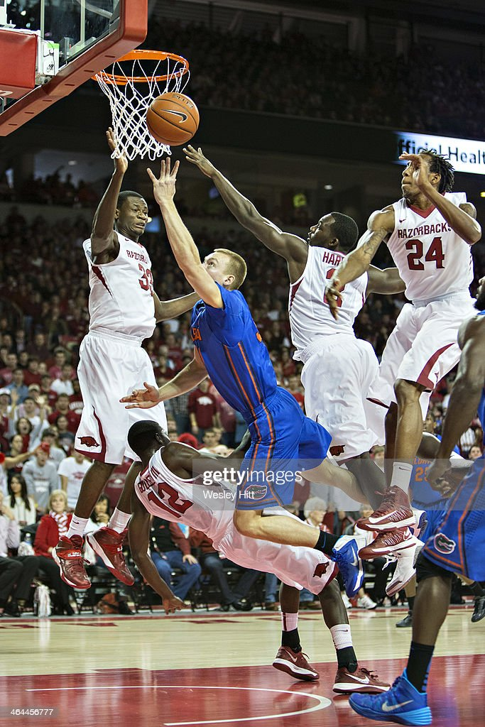 Jacob Kurtz #30 of the Florida Gators goes up for a shot and charges into Fred Gulley III #12 of the Arkansas Razorbacks at Bud Walton Arena on January 11, 2014 in Fayetteville, Arkansas. The Gators defeated the Razorbacks 84-82.