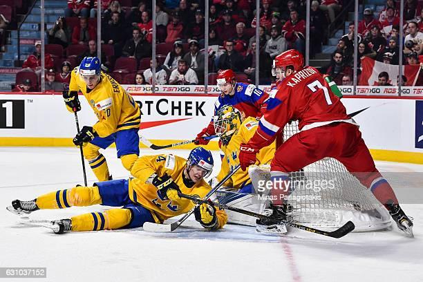 Jacob Larsson of Team Sweden helps defend the net of goaltender Felix Sandstrom from Kirill Kaprizov of Team Russia during the 2017 IIHF World Junior...