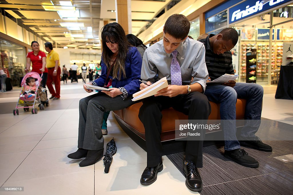 Jacob Makoulian (C) and Maria Toro (L) fill out job application forms as they apply for jobs during a job fair at Sawgrass Mills on October 11, 2013 in Sunrise, Florida. As the holiday season approaches many of the roughly 50 retailers at the job fair including Banana Republic, J.Crew Factory, Victoria's Secret and Calvin Klein are starting to hire people for seasonal work as well as continuing to look for qualified full time employees.