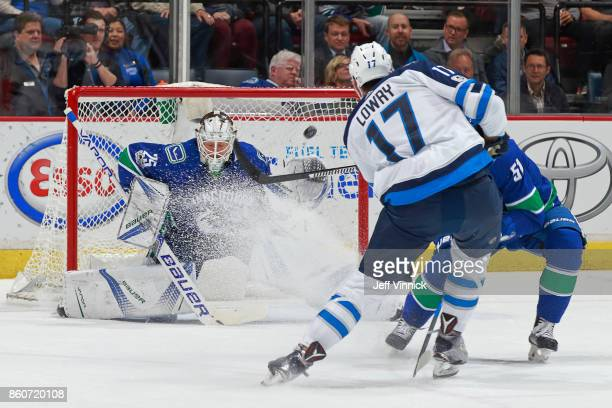 Jacob Markstrom of the Vancouver Canucks blocks a shot from Adam Lowry of the Winnipeg Jets during their NHL game at Rogers Arena October 12 2017 in...