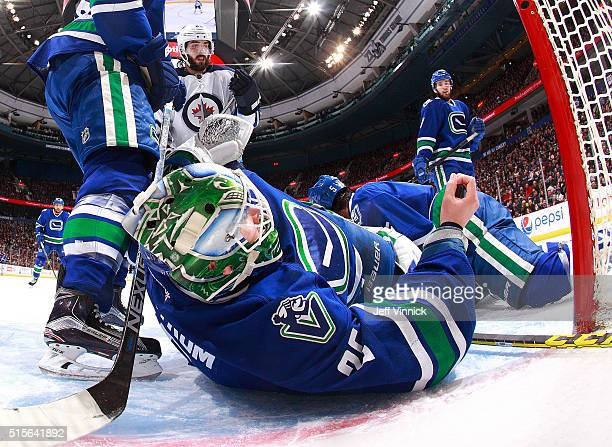 Jacob Markstrom of the Vancouver Canucks holds the puck in his hand after making a save with his bare hand after losing his blocker during their NHL...