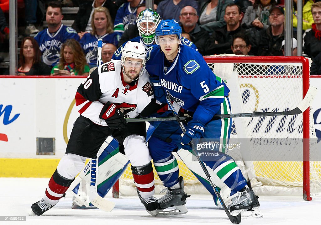 Jacob Markstrom of the Vancouver Canucks peaks between Antoine Vermette of the Arizona Coyotes and Luca Sbisa of the Canucks during their NHL game at...