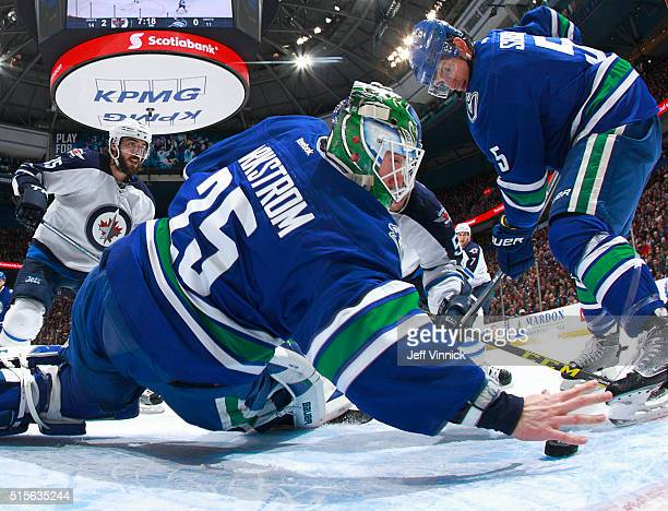 Jacob Markstrom of the Vancouver Canucks reaches back with his bare hand to make a save as Mathieu Perreault of the Winnipeg Jets and Luca Sbisa of...