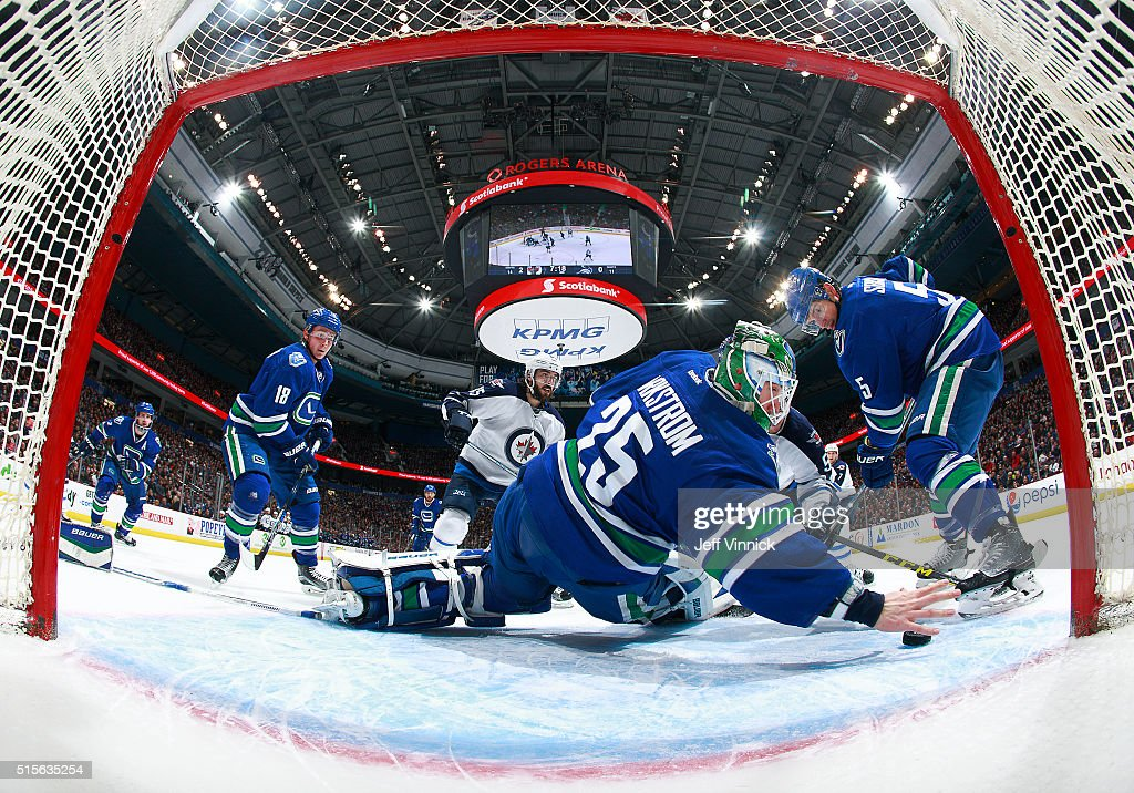 Jacob Markstrom #25 of the Vancouver Canucks reaches back with his bare hand to make a save as Mathieu Perreault #85 of the Winnipeg Jets, Jake Virtanen #18 and Luca Sbisa #5 of the Vancouver Canucks watch during their NHL game at Rogers Arena March 14, 2016 in Vancouver, British Columbia, Canada.