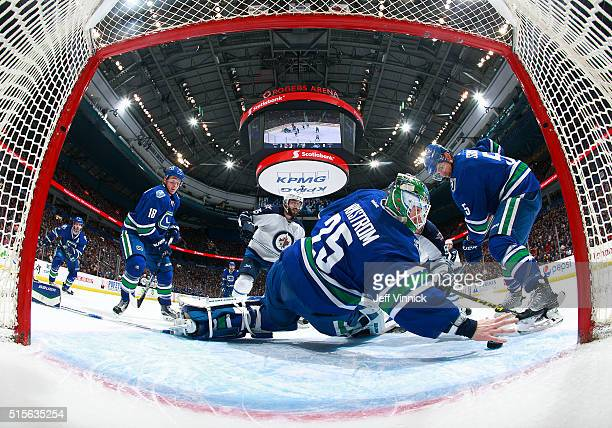 Jacob Markstrom of the Vancouver Canucks reaches back with his bare hand to make a save as Mathieu Perreault of the Winnipeg Jets Jake Virtanen and...
