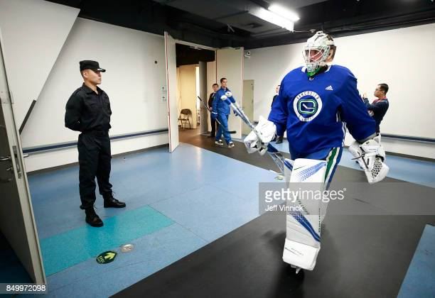 Jacob Markstrom of the Vancouver Canucks walks past a Chinese soldier before their practice at MercedesBenz Arena September 20 2017 in Shanghai China...