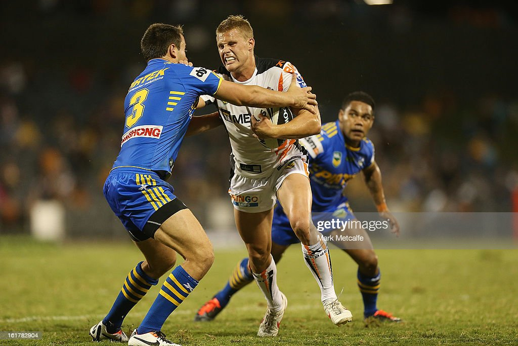 Jacob Miller of the Tigers is tackled during the NRL trial match between the Wests Tigers and the Parramatta Eels at Campbelltown Sports Stadium on February 16, 2013 in Sydney, Australia.