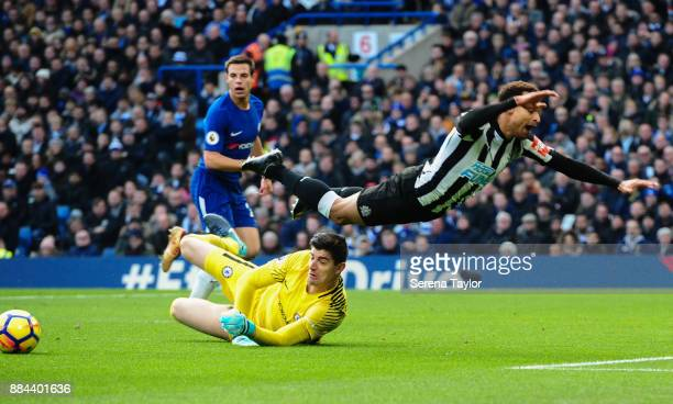 Jacob Murphy of Newcastle United flies through the air as Chelsea Goalkeeper Thibaut Courtois makes a save during the Premier League match between...