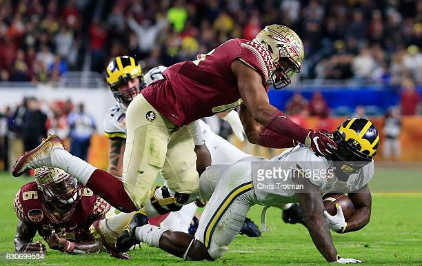 Jacob Pugh of the Florida State Seminoles grabs the face mask of De'Veon Smith of the Michigan Wolverines in the third quarter during the Capitol One...